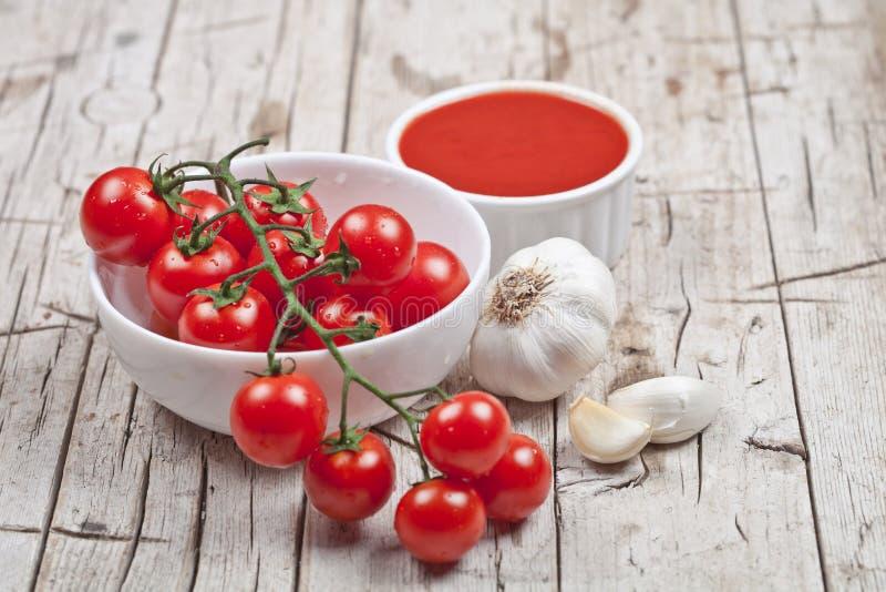 Frische Tomaten in der weißen Schüssel, in der Soße und im rohen Knoblauch auf rustikalem Holztisch stockfoto