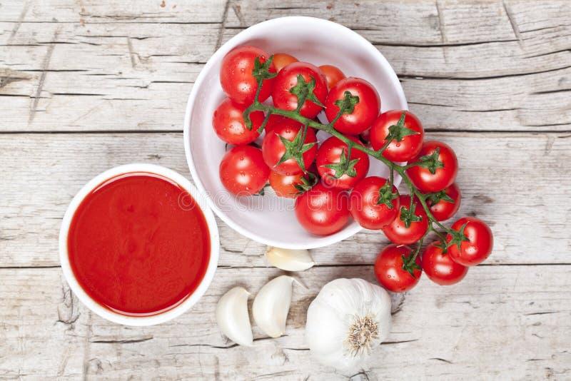 Frische Tomaten in der wei?en Sch?ssel, in der So?e und im rohen Knoblauch auf rustikalem Holztisch lizenzfreie stockfotos