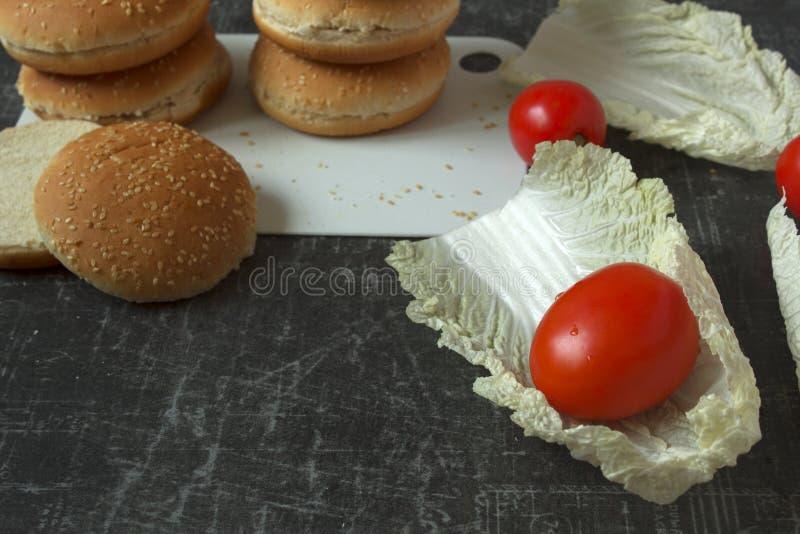 Frische Tomaten-, Kopfsalat- und Burgerbrötchen mit Samen des indischen Sesams auf einem hackenden Brett stockbild