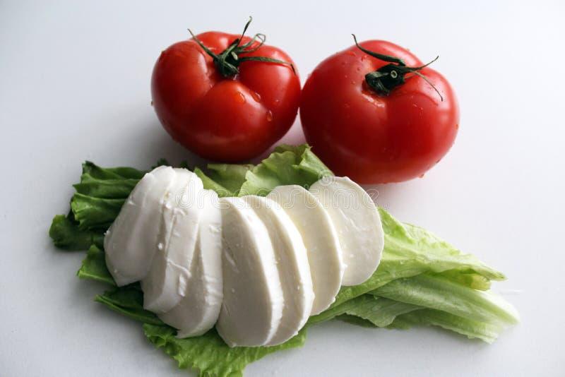 Frische Tomaten mit grünen Ausschnitten und geschnittener Mozzarellakäse auf Salatblättern stockfotografie