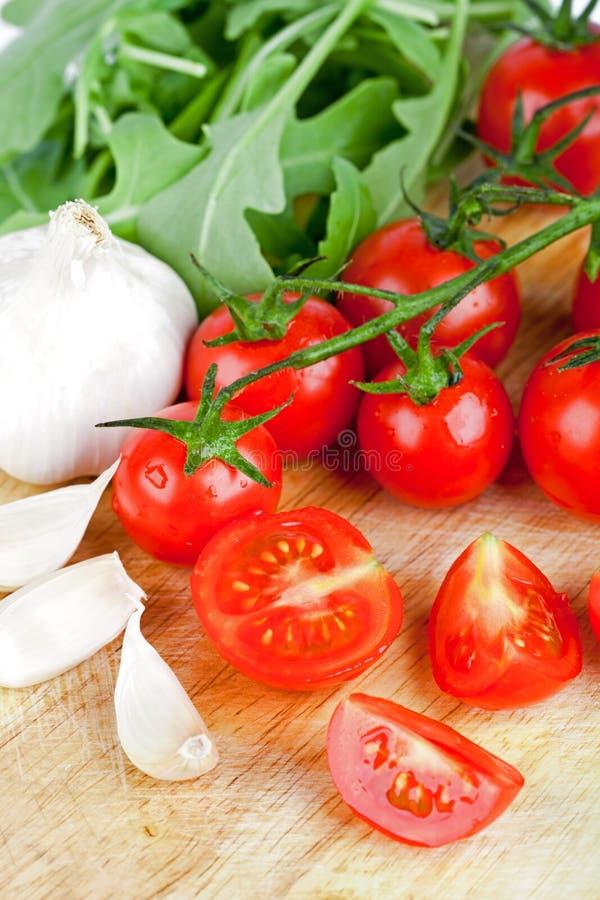 Frische Tomaten, rucola und Knoblauch lizenzfreie stockfotografie