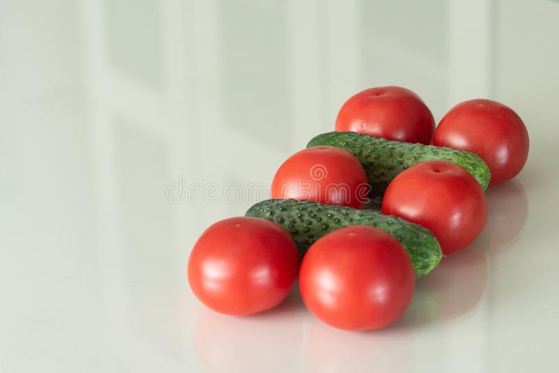 Frische Tomaten und Gurke auf einem weißen Glasküchentisch Frische Bestandteile des biologischen Lebensmittels Beschneidungspfad  stockfotos
