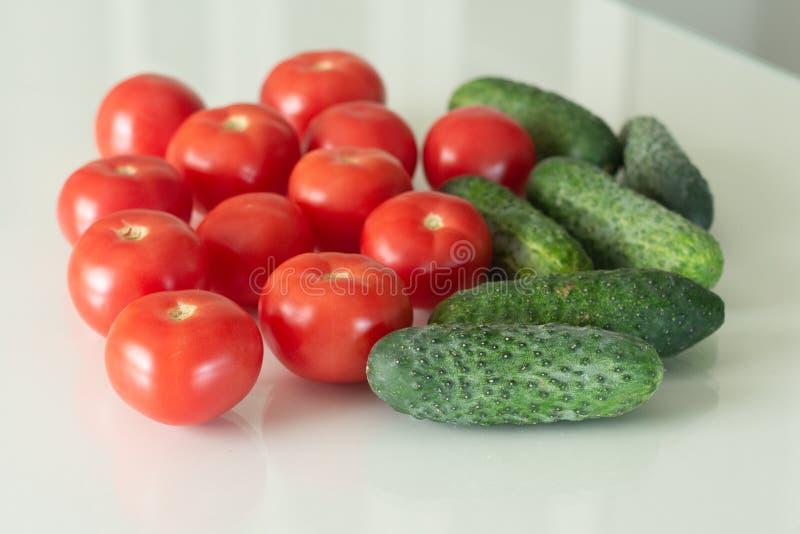 Frische Tomaten und Gurke auf einem weißen Glasküchentisch Frische Bestandteile des biologischen Lebensmittels Beschneidungspfad  lizenzfreie stockfotos