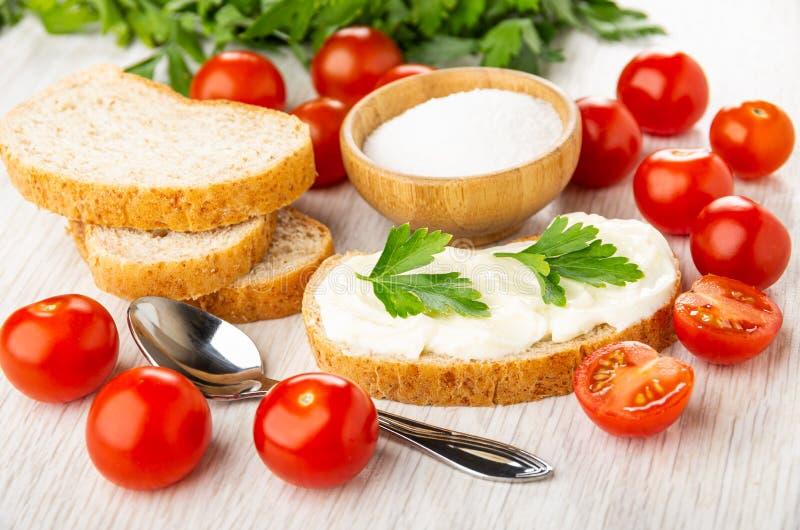 Frische Tomatenkirsche, Schüssel mit Salz, Stücke Brot, Sandwich mit geschmolzenem Käse, Löffel, Petersilie auf Tabelle lizenzfreies stockbild