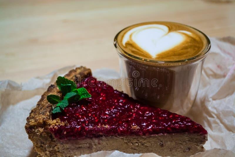 Frische Torte des Stückes Himbeermit Cappuccino im transparenten Glas mit Herzen Lattekunst Frischer Kaffee und guter Morgen in d lizenzfreie stockfotografie