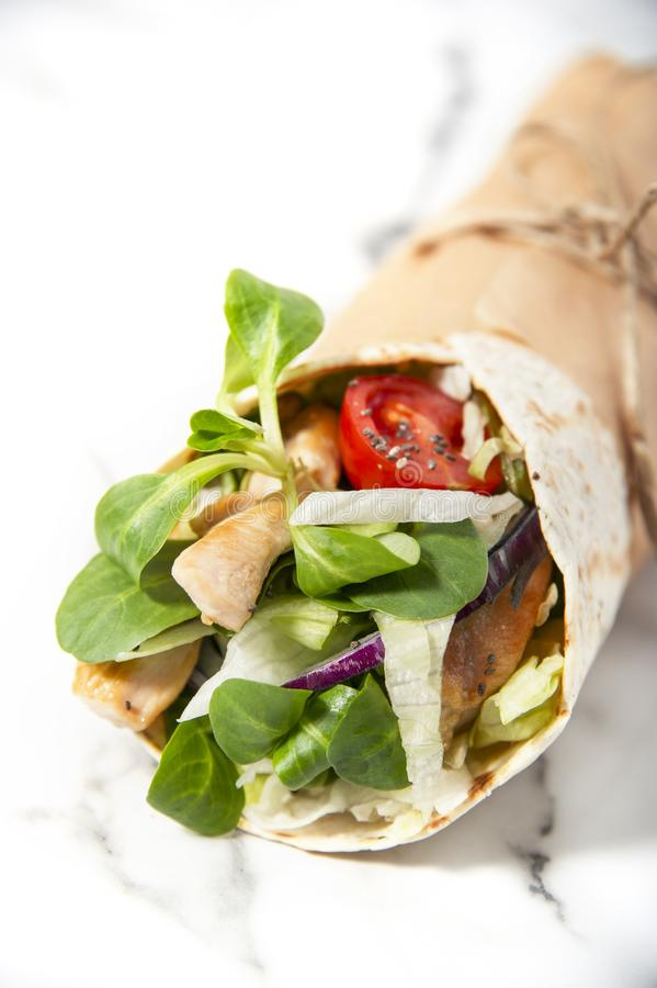 Frische Tortillaverpackung mit Gemüse und gebratenem Huhn lizenzfreie stockfotografie