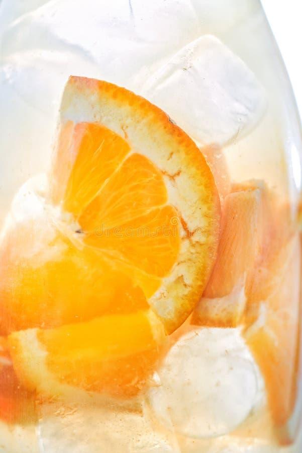 Frische tropische oder Sommerlimonade mit Orange und Eis im Glas, Detailphotographie, abstrakt stockfotografie