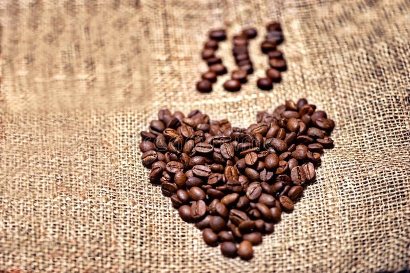Frische und aromatische Kaffeebohnen auf Weinlesestoff lizenzfreies stockbild