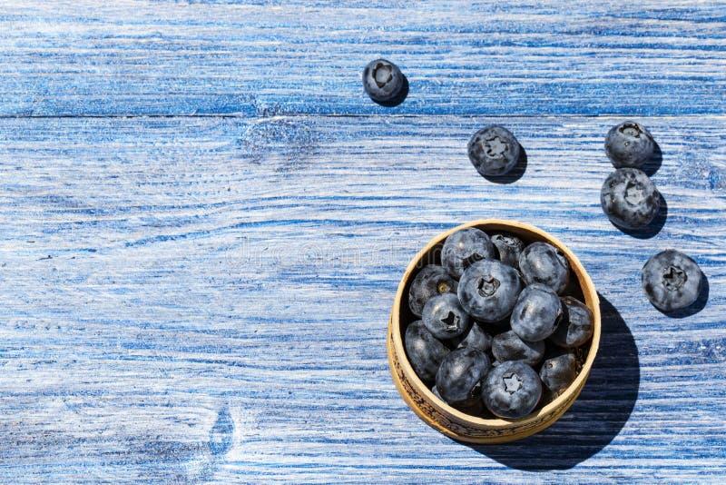 Frische und saftige Blaubeeren in einer weißen Schüssel auf blauem Holztisch mit copyspace Gesundes Nahrungsmittelkonzept Draufsi stockbild