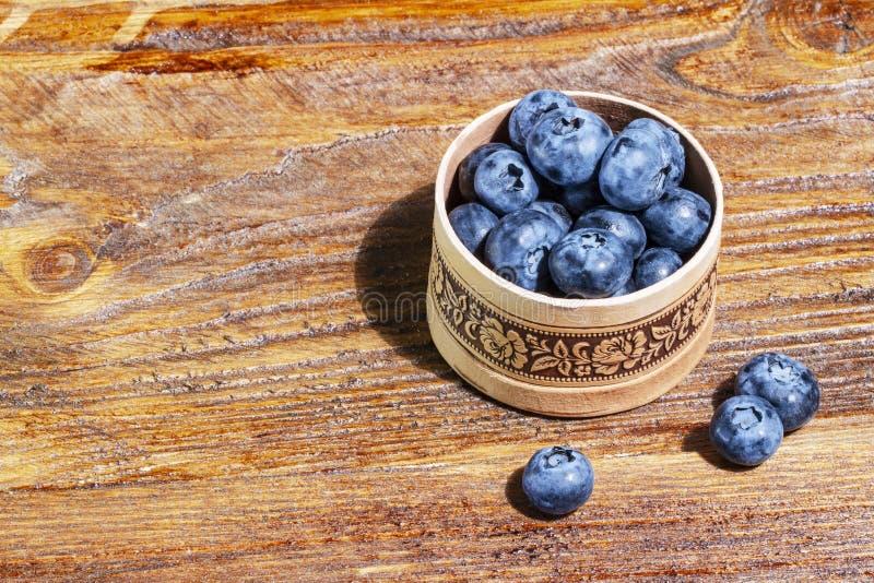 Frische und saftige Blaubeeren in einer wei?en Sch?ssel auf Holztisch mit copyspace Gesundes Nahrungsmittelkonzept Kopieren Sie P stockfoto