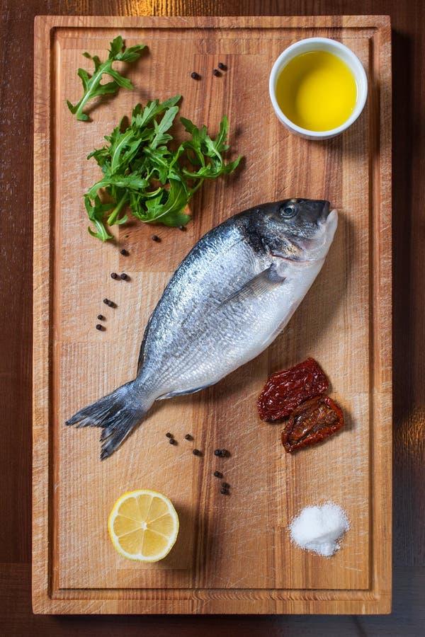 Frische ungekochte dorado Fische mit Bestandteilen auf dem hölzernen Brett lizenzfreie stockbilder