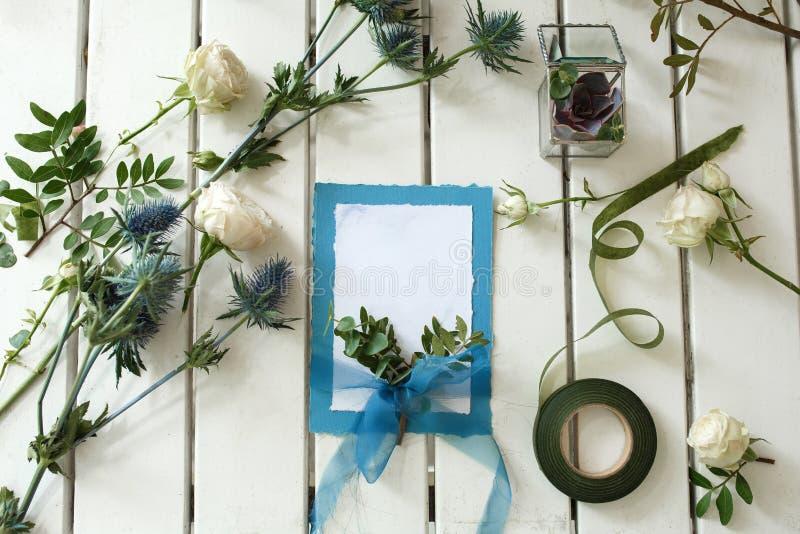 Frische weiße Rosen und Heiratseinladungskarte auf weißem hölzernem ta lizenzfreie stockbilder