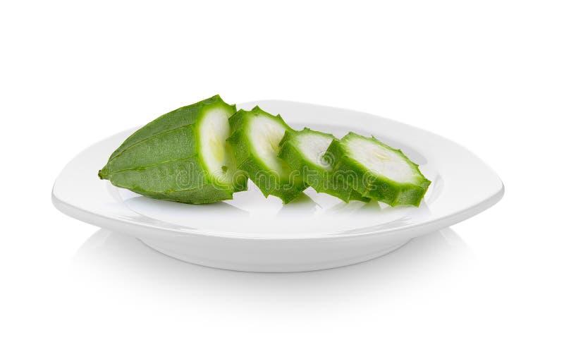 Frische winklige Luffaschwammfrucht in der keramischen weißen Platte auf weißem backgro stockbild