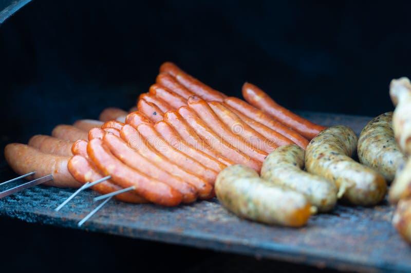 Frische Wurst und Hotdoge, die draußen grillen lizenzfreie stockbilder