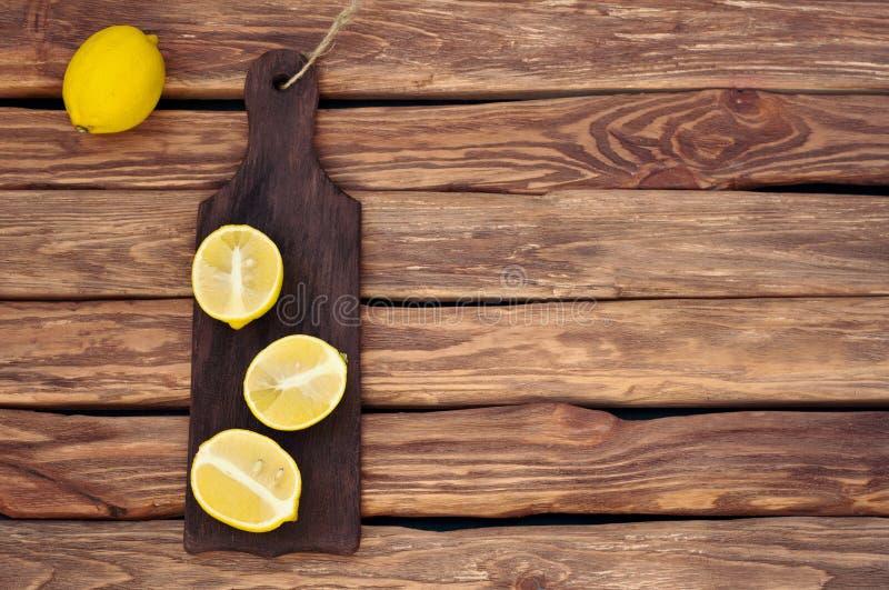 Frische Zitrone auf einem kleinen hackenden Brett auf dem alten Holztisch stockfoto