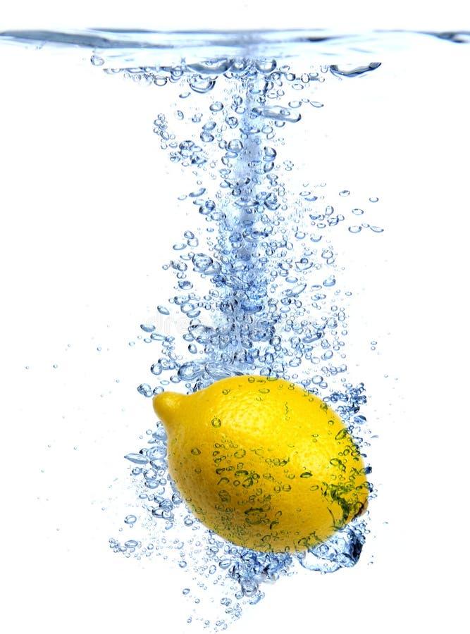 Frische Zitrone fiel in Wasser stockbilder