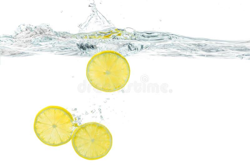 Frische Zitrone fiel in Wasser mit dem Spritzen, das auf Weiß lokalisiert wurde stockfoto