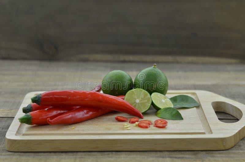 Frische Zitrone mit Paprika schnitt Scheiben im Brett auf hölzernem Hintergrund stockfoto