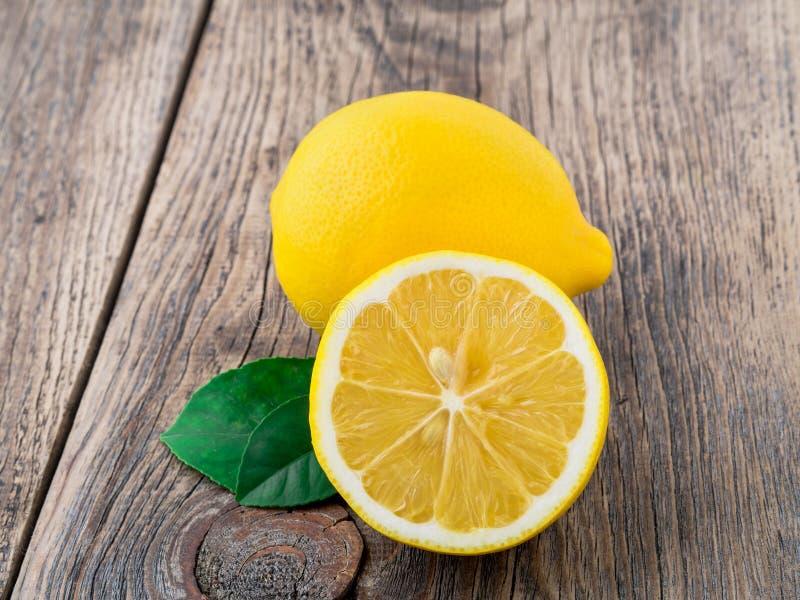 Frische Zitrone und abgeschnittene Hälfte auf hölzerner alter Tabelle, Seitenansicht lizenzfreie stockfotos