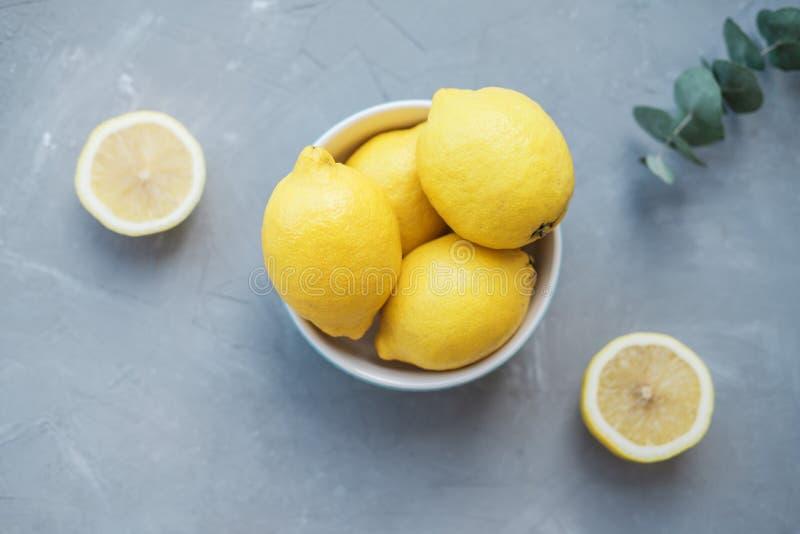 Frische Zitronen in einer blauen Schüssel auf einem grauen Hintergrund stockbilder