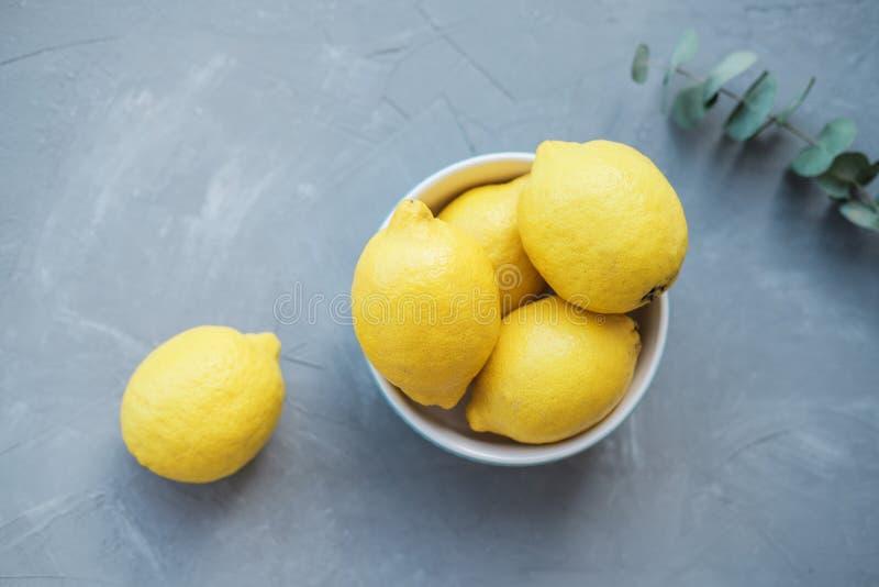 Frische Zitronen in einer blauen Schüssel auf einem grauen Hintergrund stockfotos