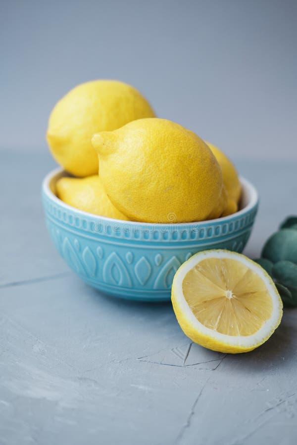 Frische Zitronen in einer blauen Schüssel auf einem grauen Hintergrund lizenzfreie stockfotos