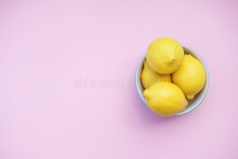 Frische Zitronen in einer blauen Schüssel auf einem rosa Hintergrund stockfoto