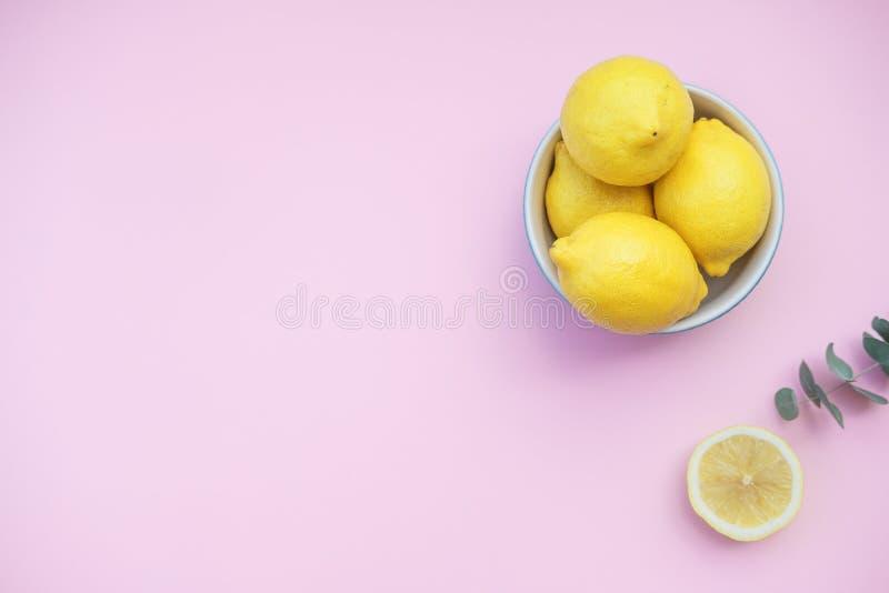 Frische Zitronen in einer blauen Schüssel auf einem rosa Hintergrund lizenzfreies stockbild