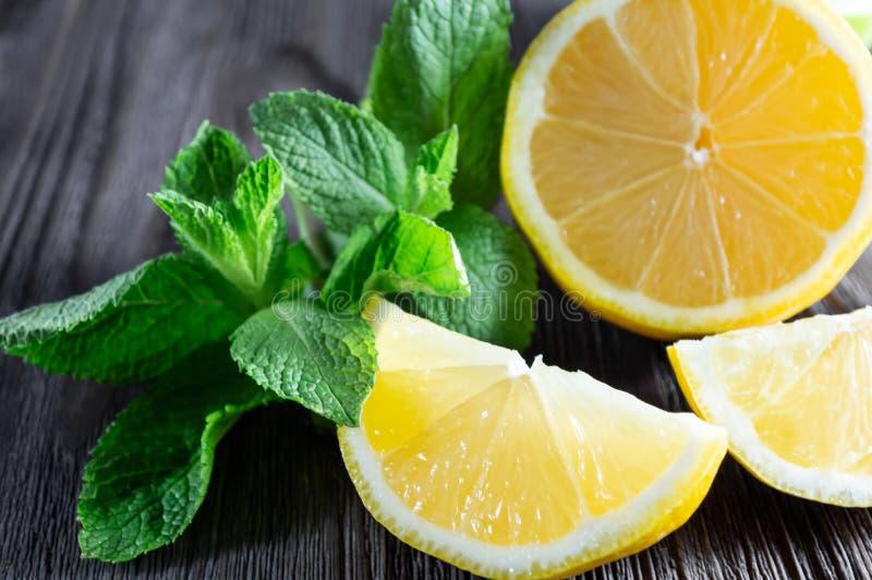Frische Zitronen und tadellose Blätter auf dunklem hölzernem Hintergrund lizenzfreies stockbild