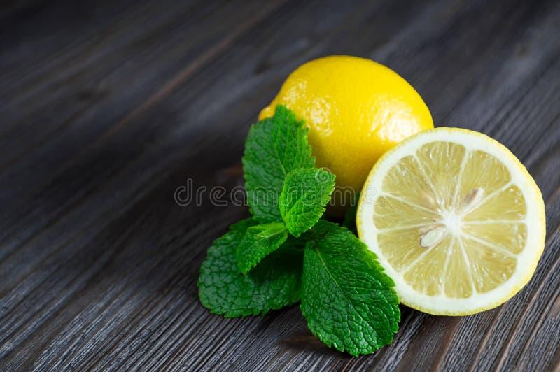 Frische Zitronen und tadellose Blätter auf einem dunklen hölzernen Hintergrund lizenzfreies stockfoto