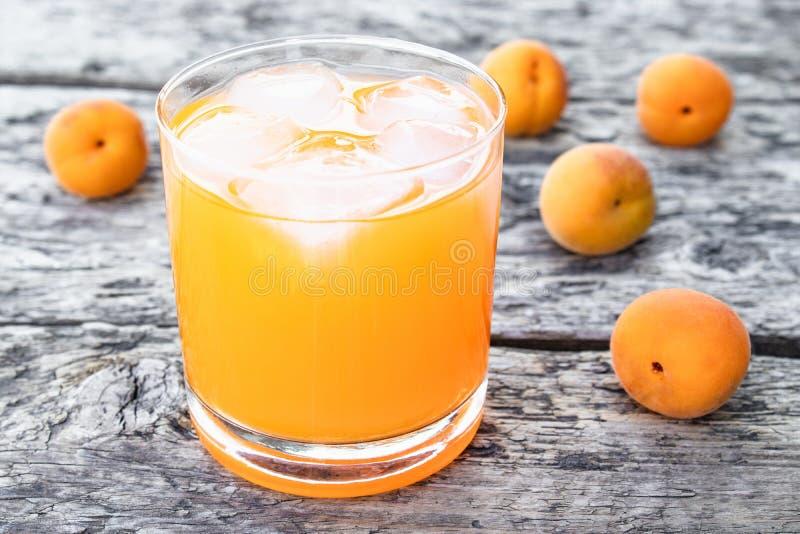 Frischer Aprikosensaft mit Aprikosen und Eiswürfeln in einem Glas vor dem hintergrund der alten Bretter Sommeralkoholfreie getr?n stockfotografie