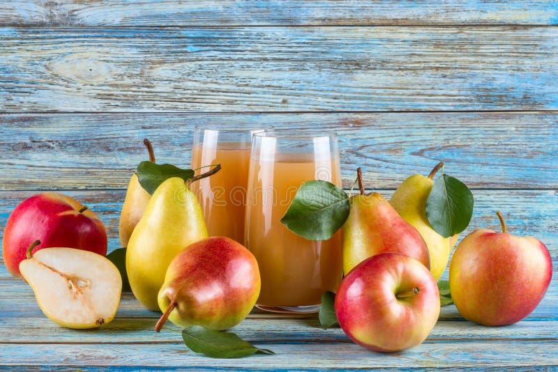Frischer Biohofbirneapple-Saft im Glas mit rohen ganzen geschnittenen Birnen und Äpfeln stockfotografie