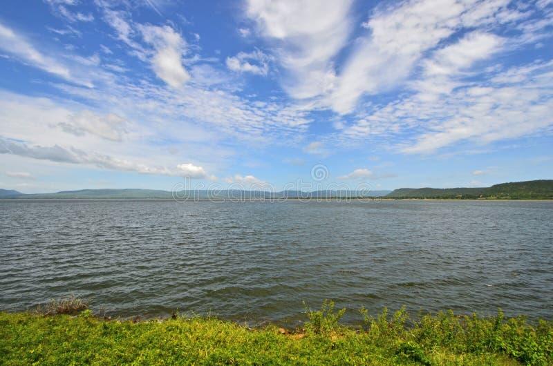 Frischer blauer Himmel und helle weiße Wolken über den Bergen und dem See stockfotografie
