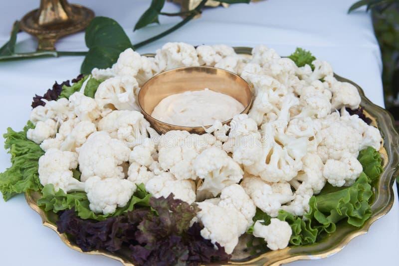 Frischer Blumenkohl mit Käsesoßen- und -salatblättern auf Tabelle, Nahaufnahme stockbild