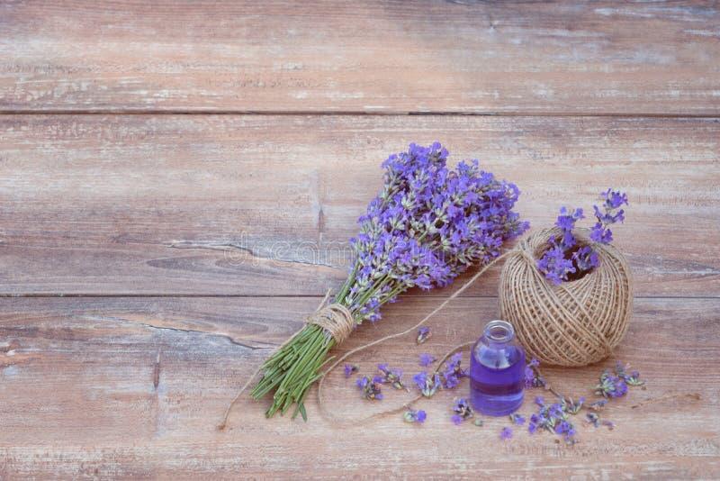 Frischer Blumenstrauß des Lavendels, des Hanfballs und des Lavendelätherischen öls auf braunem hölzernem Hintergrund lizenzfreie stockfotografie