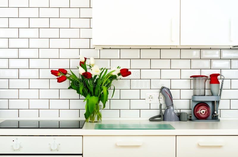 Frischer Blumenstrauß von roten und weißen Tulpen auf Küchentisch Detail des Hauptinnenraums, Design Minimalistic-Konzept Blumen lizenzfreie stockfotografie