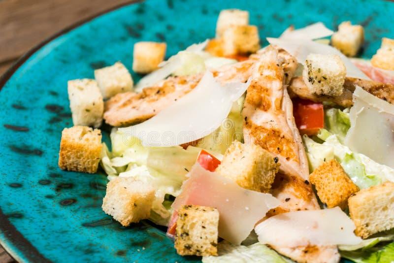 Frischer Caesar-Salat in der grünen Platte auf Holztisch stockfotos