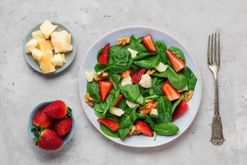 Frischer Erdbeersalat mit Spinatsblättern, Parmesankäseparmesankäse und Walnüssen mit Gabel gesunde Keton-Di?tnahrung lizenzfreie stockbilder