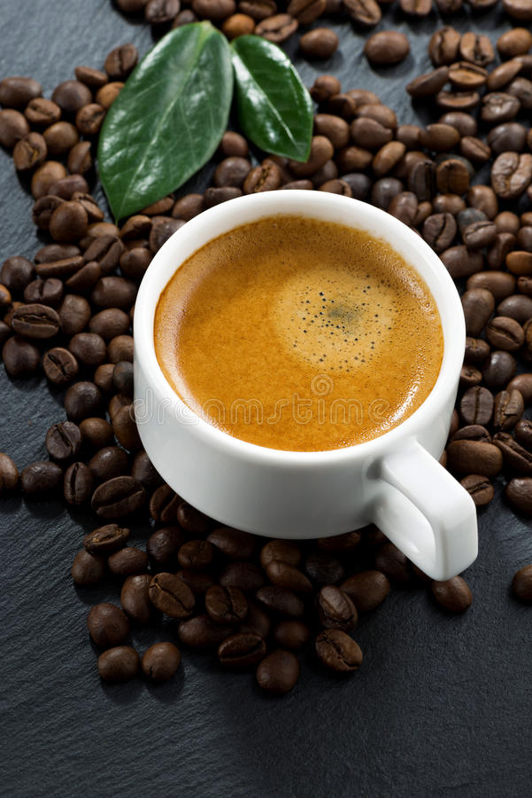 Frischer Espresso auf Kaffeebohnehintergrund, Vertikale, Draufsicht stockbild