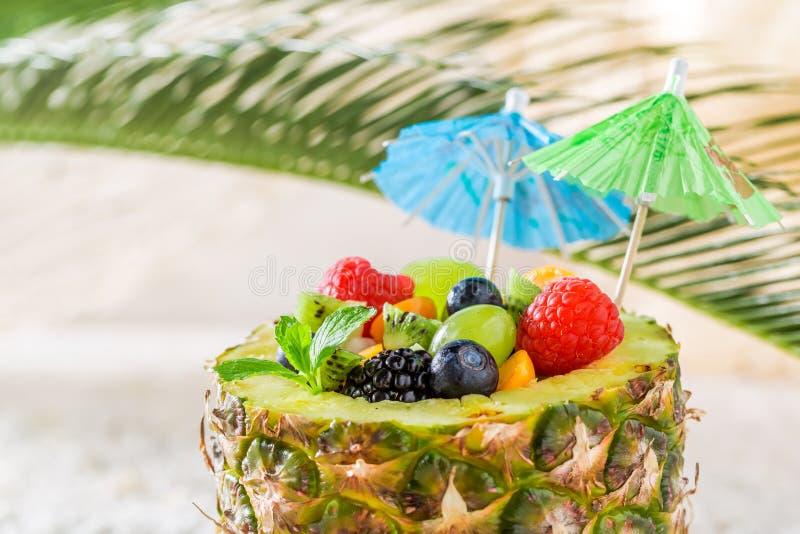 Frischer Fruchtsalat in der Ananas mit Cocktailregenschirmen stockfotografie