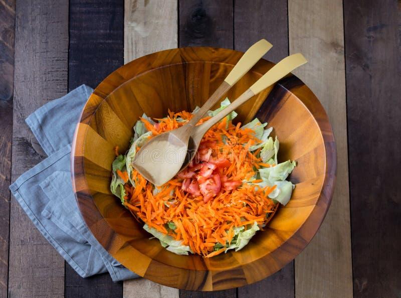 Frischer Gartensalat in der hölzernen Schüssel auf hölzernem Hintergrund lizenzfreies stockfoto