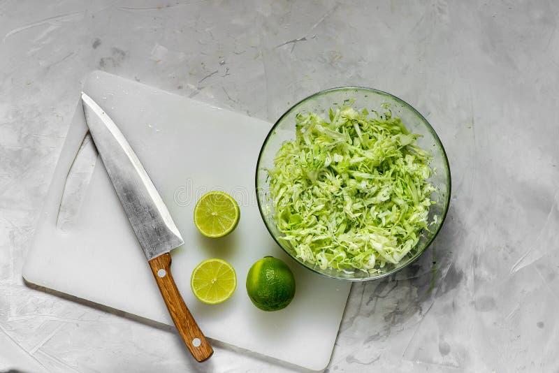 Frischer gehackter Kohl für Salat und Scheiben des frischen Kalkes stockfotos