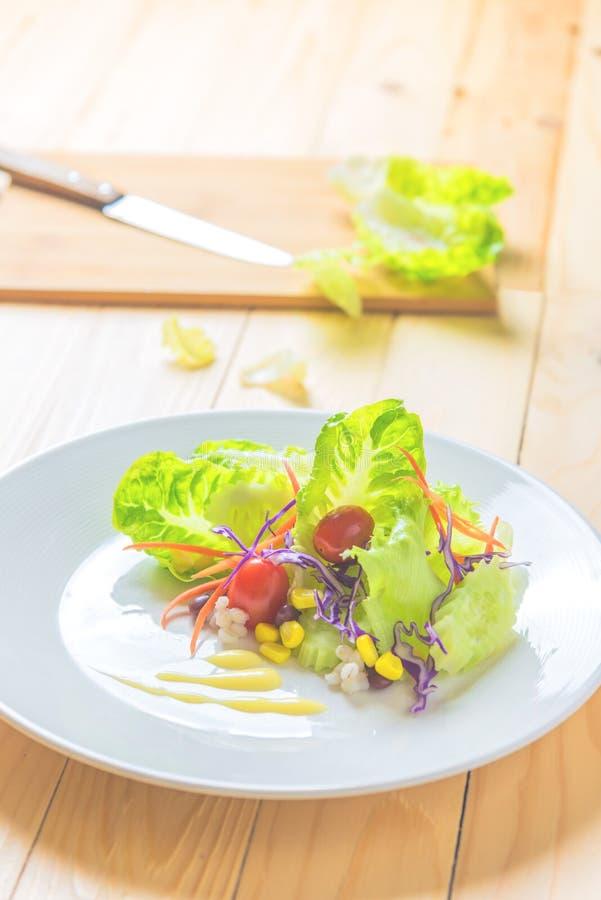 Frischer gesunder Salat auf Holztisch stockfotografie