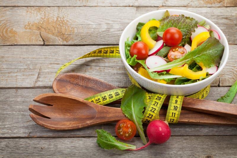 Frischer gesunder Salat, Gerät und Maßband stockfoto