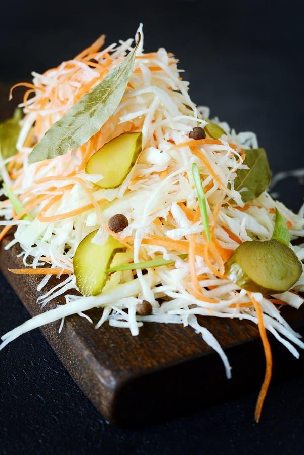 Frischer gesunder Salat - Kohl, Karotte, Essiggurke Kohlsalat auf einem hölzernen Brett auf einem hellen Hintergrund Gemüse für F stockbilder
