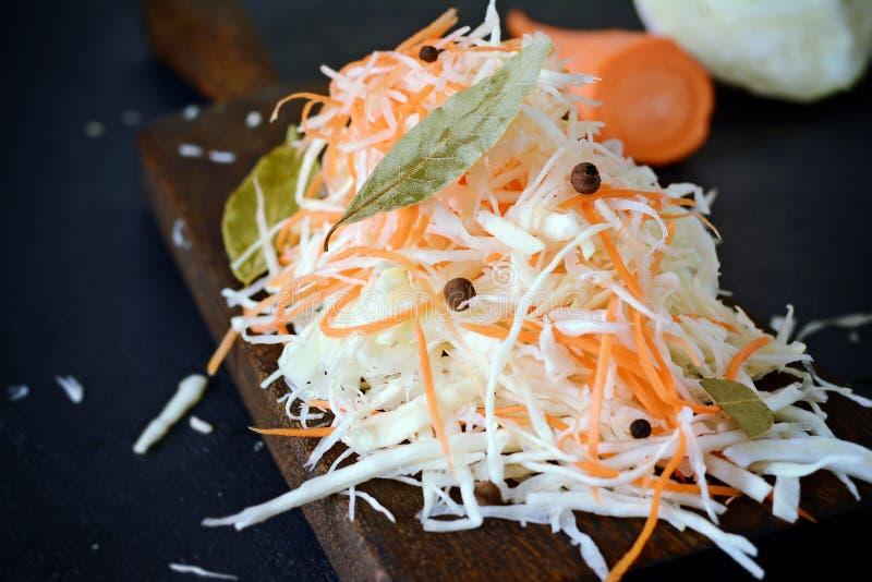 Frischer gesunder Salat - Kohl, Karotte Kohlsalat auf einem hölzernen Brett auf einem hellen Hintergrund Gemüse für Ferment stockfoto