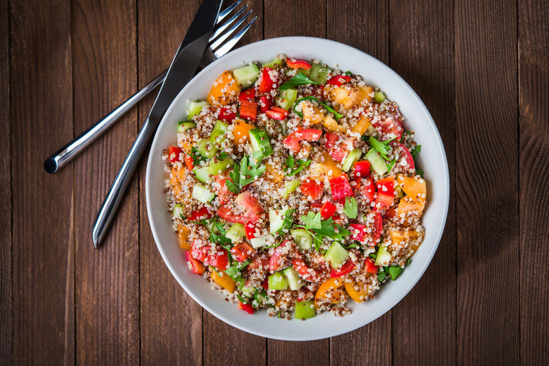 Frischer gesunder Salat mit Quinoa, bunten Tomaten, Gemüsepaprika, Gurke und Petersilie auf Draufsicht des hölzernen Hintergrunde lizenzfreies stockfoto