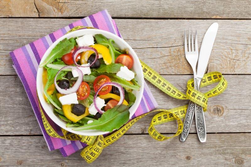 Frischer gesunder Salat, Tafelsilber und Maßband stockfotos