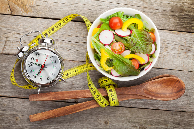 Frischer gesunder Salat und messendes Band auf Holztisch lizenzfreies stockfoto