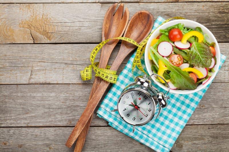 Frischer gesunder Salat und messendes Band auf Holztisch stockbilder